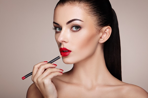 Beautiful Russian woman paints her lips with a red lipstick looking at the camera