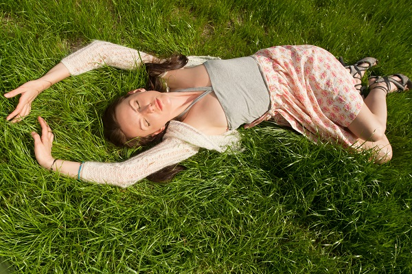 Young attractive Russian woman lying on green grass while posing for the camera