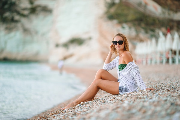 Gorgeous Russian woman lying on the beach enjoying her summer holidays looking at the sea