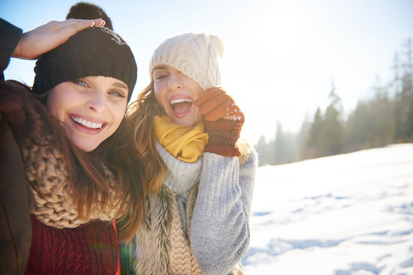 Two young extremely attractive Russian females walking together in a winter forest
