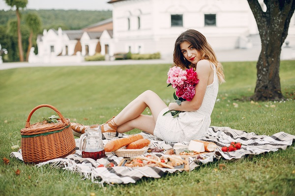 Elegant and stylish Russian girl sitting with flowers in a summer garden