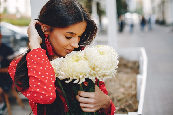 Elegant Russian brunette with a nice bouquet of white flowers in a summer city