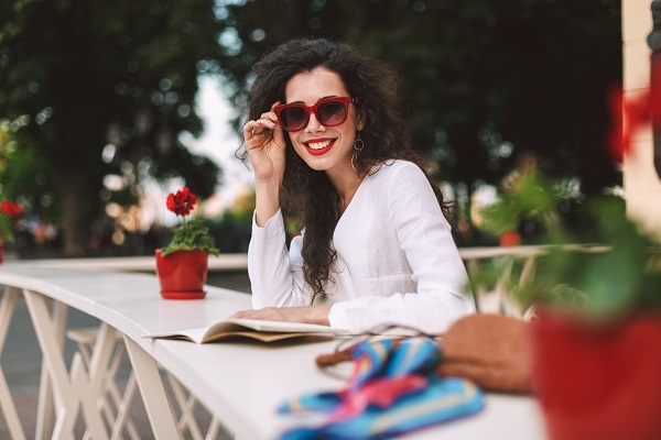 Young smiling Russian lady in sunglasses happily looking in a camera sitting in a summer cafe