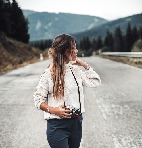 Outdoor fashionable photo of a young beautiful Russian lady walking with a camera
