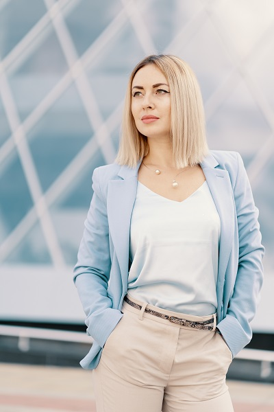 Successful Russian businesswoman standing in a blue suit with her hands in the pockets