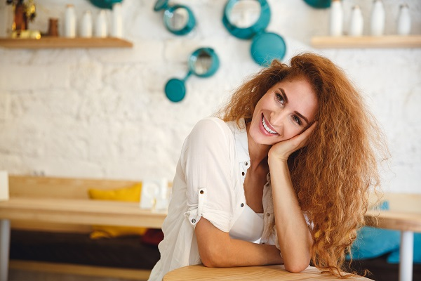 Pretty redhead young Russian lady sitting in a cafe while posing for the camera