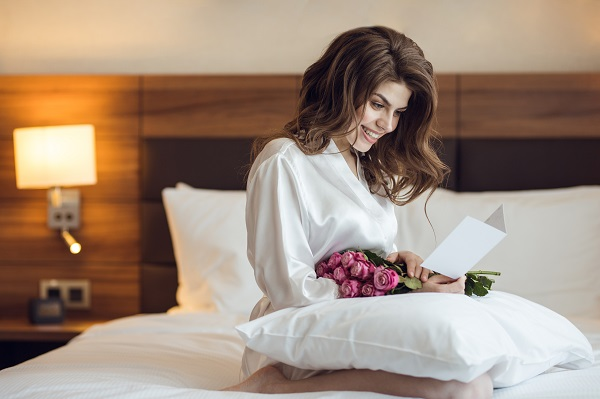Young smiling Russian woman sitting on her bed with a huge bouquet of flowers