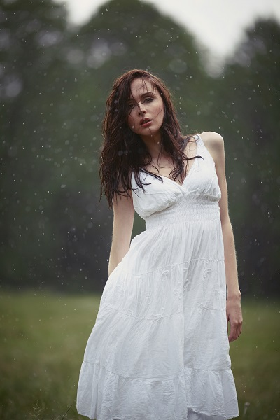 Sexy Russian lady standing under the heavy rain wearing a light white wet dress without underwear