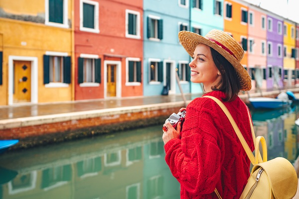 Young smiling Russian female taking a photo of colorful houses standing near the river