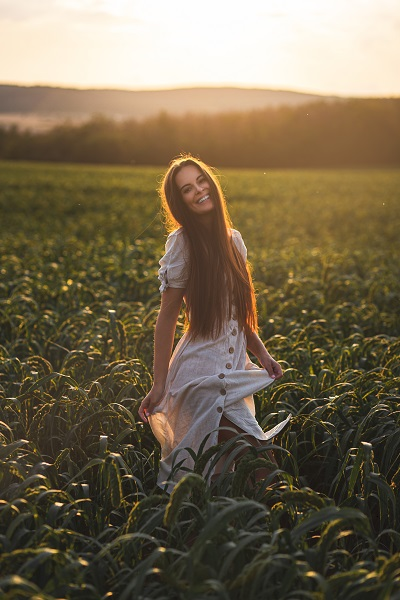 Laughing Russian female standing on a huge green field with the sunset behind her back