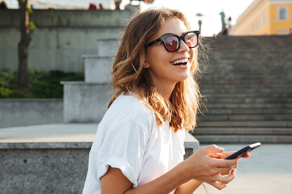 Picture of a Russian brunette woman wearing casual summer outfit while using her smartphone