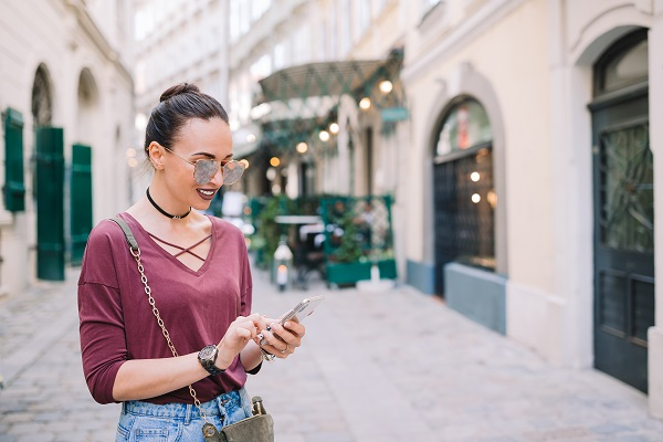 Young attractive Russian female tourist walking outdoors while using her smartphone to write friends