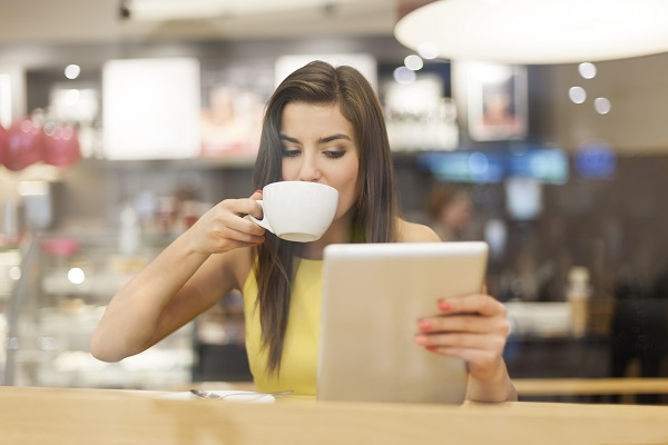 Beautiful elegant feminine Russian woman sitting using a digital tablet while sitting in a cafe