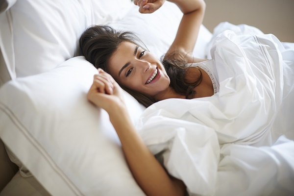 Elegant smiling Russian woman wakes up after a perfect night in her comfortable bed