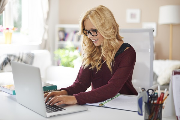 Smiling charming blonde Russian woman using her personal laptop while sitting at work